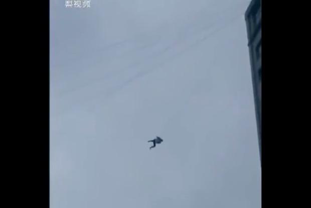 В Китае мужчина сбежал из гостиницы по проводу на высоте 19-этажного дома