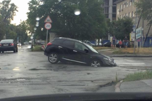 В Киеве после ливня джип утонул в огромной яме