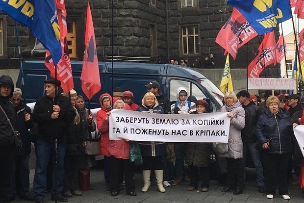 Под Кабмином разгневанные профсоюзы накормили чиновника землей