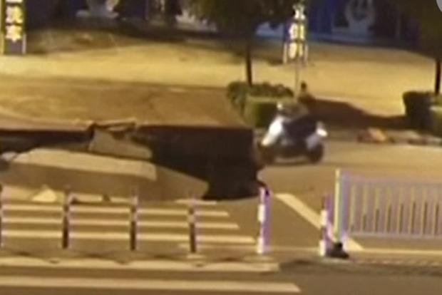 В Китае водитель скутера отвлекся на смартфон и провалился в огромную яму на дороге